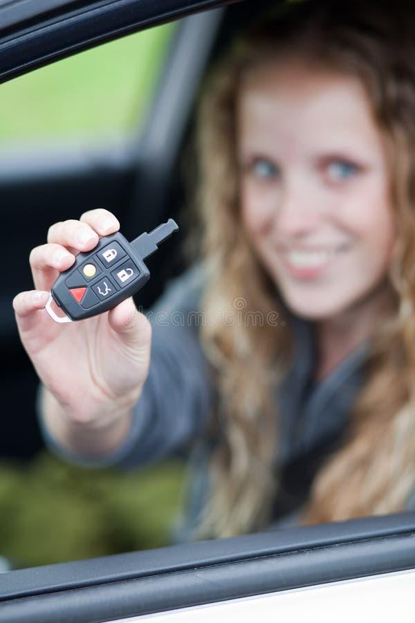 Mulher consideravelmente nova que mostra fora seu carro do tipo foto de stock royalty free