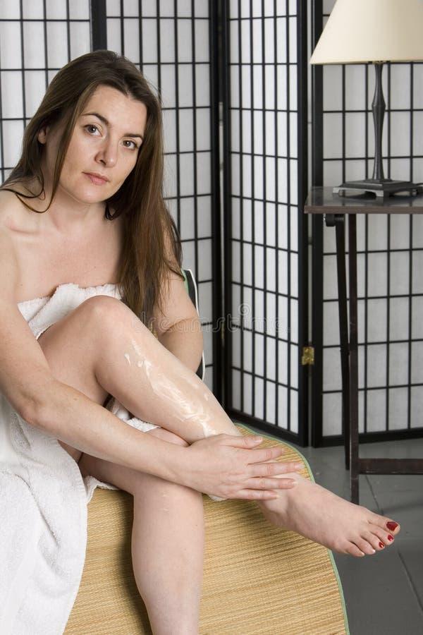 Mulher consideravelmente nova que põr sobre a loção hidratando fotografia de stock
