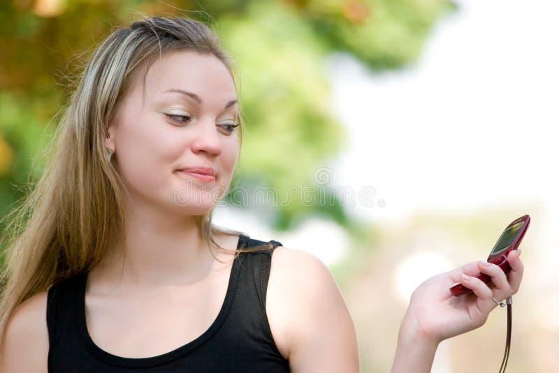 Mulher consideravelmente nova que prende o telefone móvel fotografia de stock