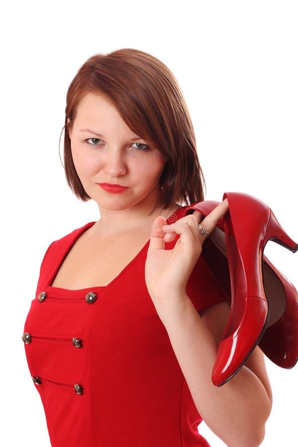 Mulher consideravelmente nova que prende sapatas vermelhas brilhantes fotografia de stock royalty free
