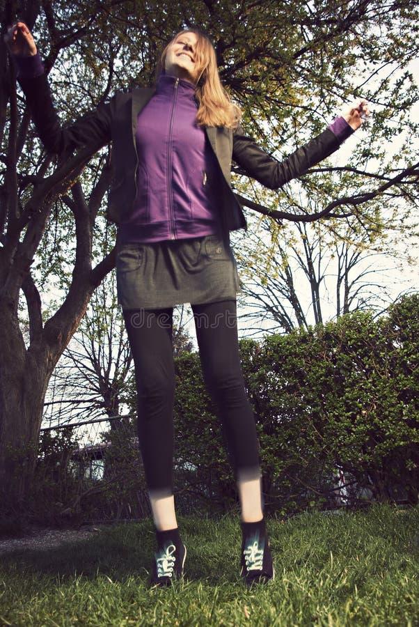 Mulher consideravelmente nova que salta na grama verde imagens de stock