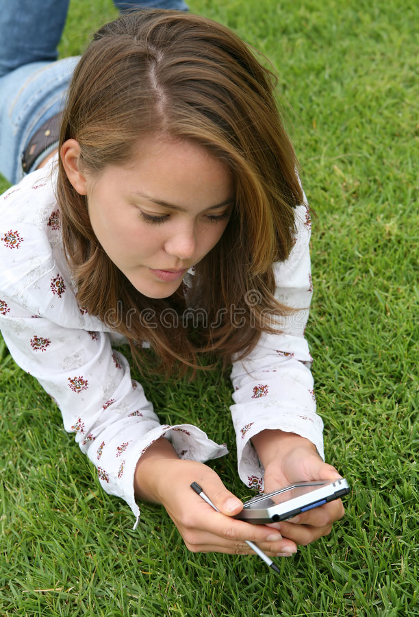 Mulher consideravelmente nova que usa um PDA fotos de stock