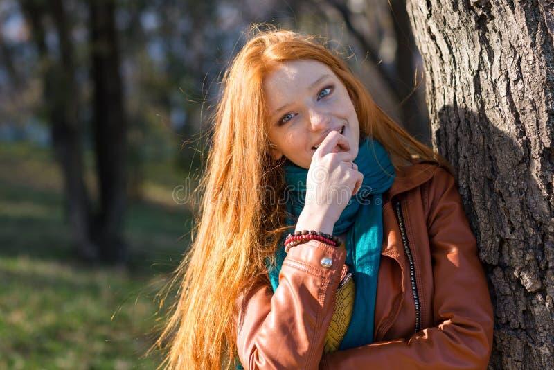 Mulher consideravelmente tímida que está perto da árvore no parque imagens de stock royalty free