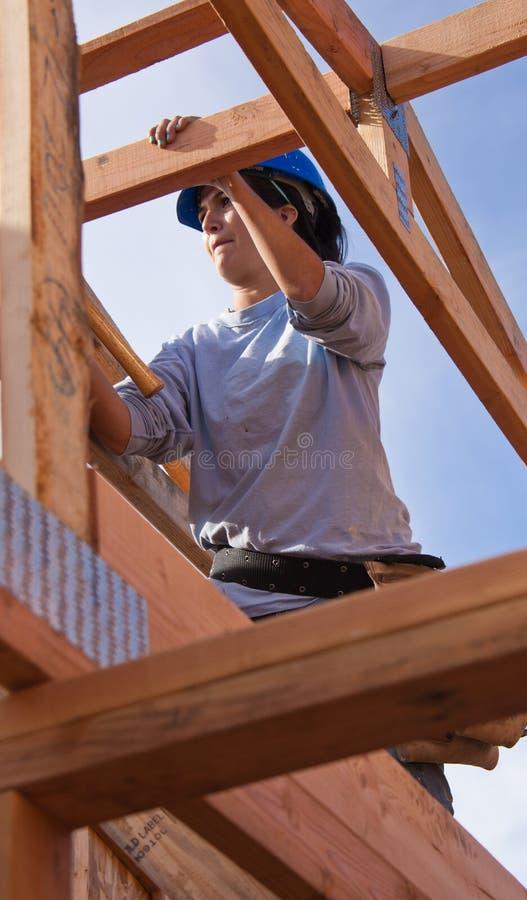 A mulher constrói o telhado para a casa para o habitat para a humanidade imagens de stock royalty free