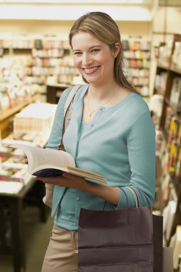 A mulher consulta em uma livraria fotografia de stock royalty free