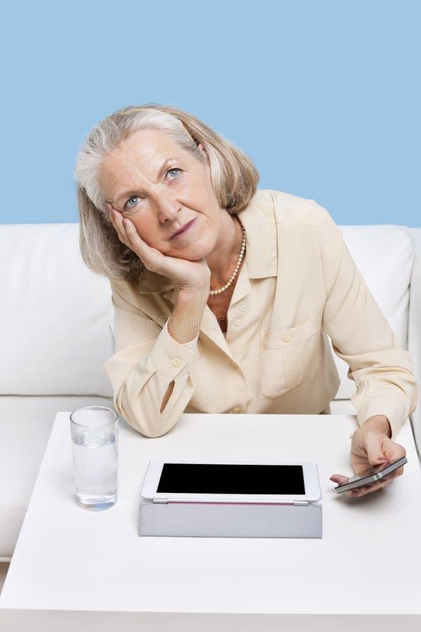 Mulher contemplativa que usa o PC do telemóvel e da tabuleta na tabela fotografia de stock royalty free