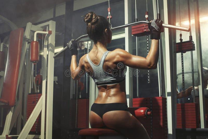 A mulher contratou no simulador no gym fotografia de stock