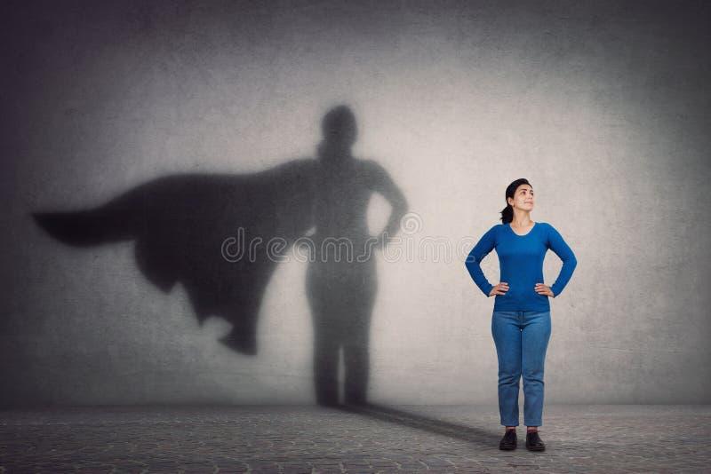 A mulher corajosa mantém braços nos quadris, sorrindo confiante, lançando um super-herói com sombra de cabo na parede Ambição e s imagens de stock