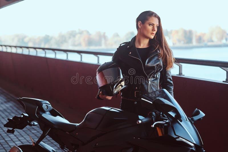 A mulher corajoso bonita está inclinando-se em seu motobike no túnel fotos de stock