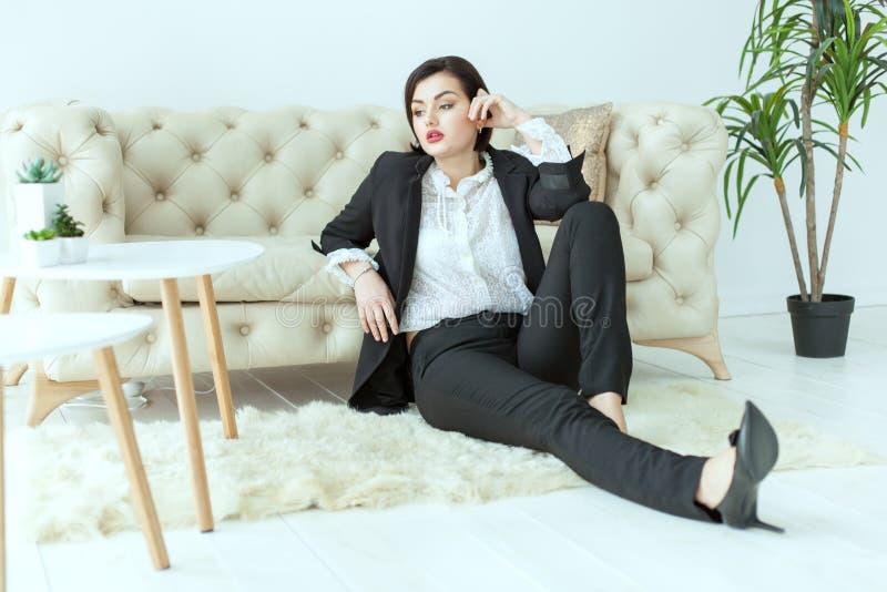 Mulher corajoso que senta-se no assoalho fotografia de stock royalty free
