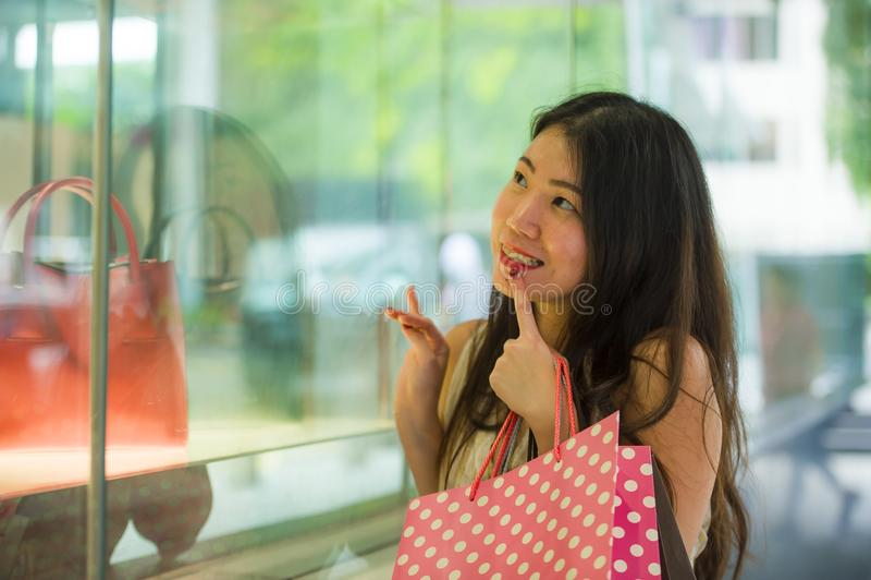 Mulher coreana asiática bonita e elegante nova que guarda sacos de compras após o passeio de compra na rua que olha entusiasmado  imagens de stock