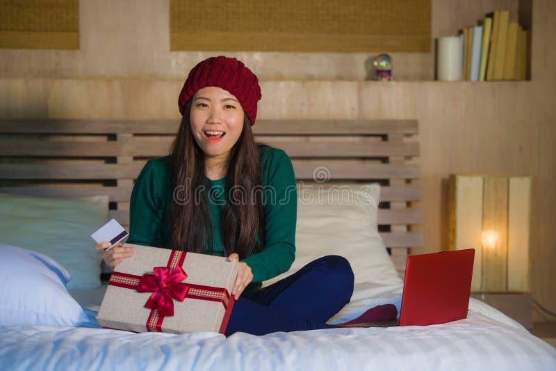 A mulher coreana asiática bonita e feliz nova que guarda o xmas em linha da compra do cartão de crédito e da caixa de presente do imagem de stock