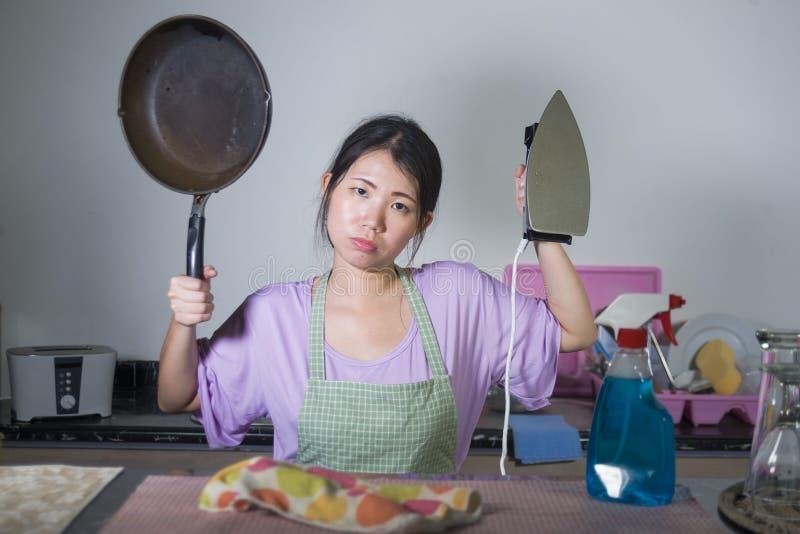 A mulher coreana asiática bonita e frustrante nova que guarda a bandeja e o ferro forçou e virou oprimido pelo trabalho e por tar imagem de stock