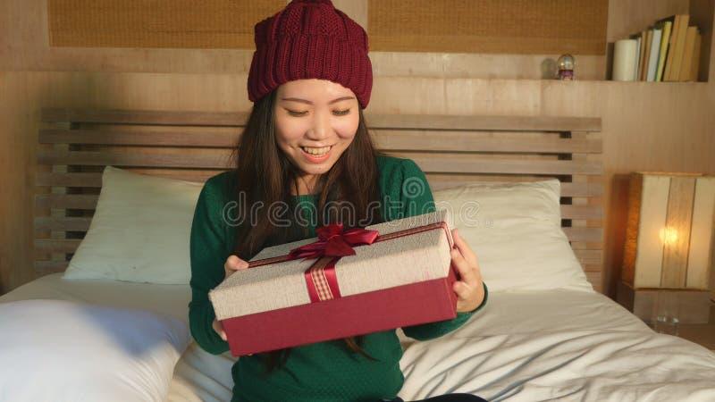 Mulher coreana asiática bonita feliz nova no chapéu do inverno que guarda o giftbox do Natal com fita que sorri receivin entusias fotos de stock