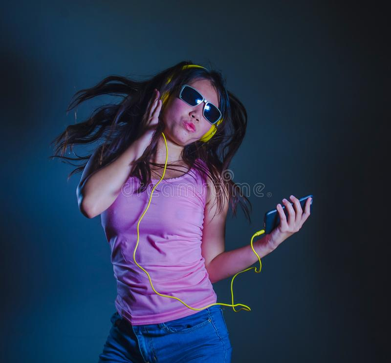 Mulher coreana asiática feliz e atrativa nova que dança e que canta à música que escuta a música com os fones de ouvido amarelos  fotos de stock royalty free