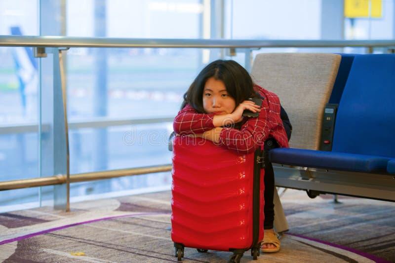 Mulher coreana asiática feliz e bonita do turista que senta-se na porta de embarque da partida do aeroporto com flig de espera da fotos de stock royalty free
