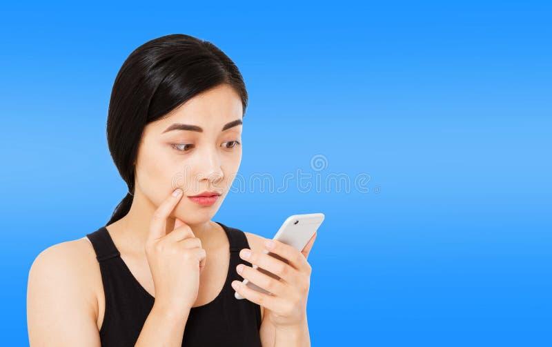 A mulher coreana, asiática lê a notícia isolou-se com cuidado em escuro - fundo azul, telefone do HOL da menina, espaço da cópia fotografia de stock