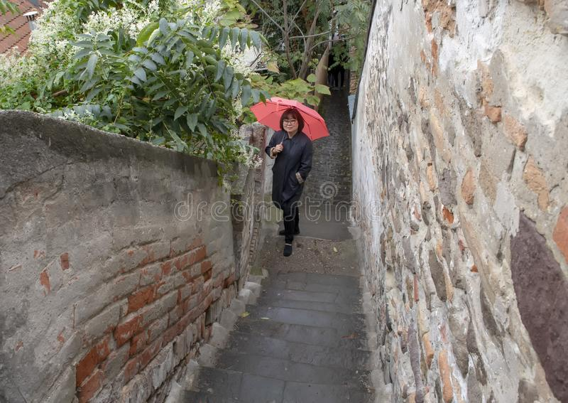 Mulher coreana com guarda-chuva cor-de-rosa em uma passagem de conexão da rua estreita, Szentendre, Hungria imagem de stock royalty free