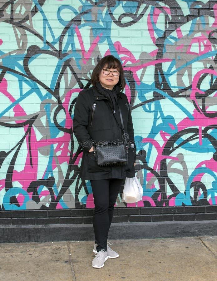 Mulher coreana na caminhada na frente de pintura mural sem assinatura no mercado italiano, Philadelphfia sul da parede, Pensilvân foto de stock