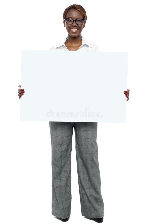 Mulher corporativa que prende o quadro de avisos branco em branco fotos de stock royalty free
