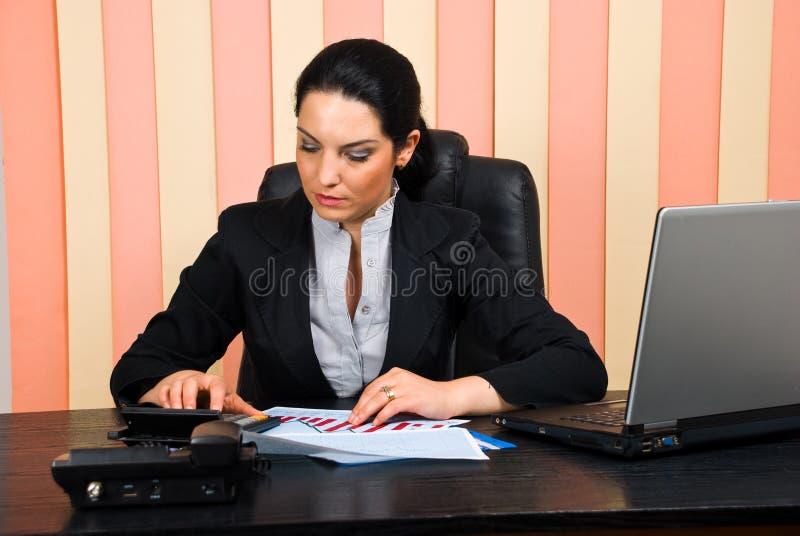 Mulher corporativa que usa a calculadora foto de stock