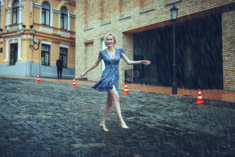 A mulher corre com os pés descalços na estrada na chuva foto de stock