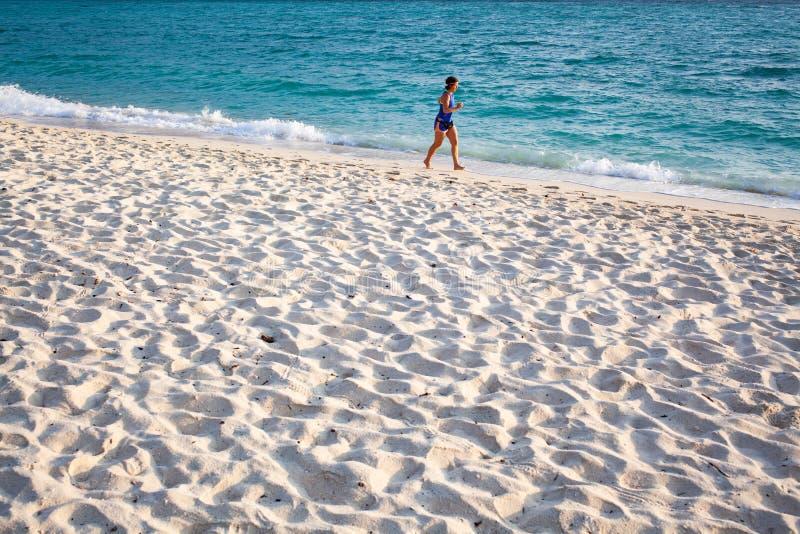 mulher a correr pelo mar - um estilo de vida ativo saudável fotografia de stock royalty free