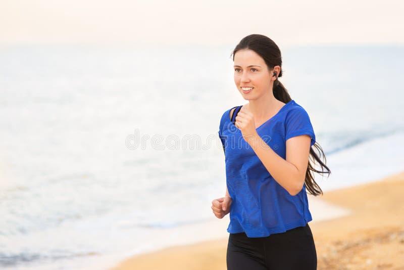 Mulher corrida na praia imagem de stock royalty free