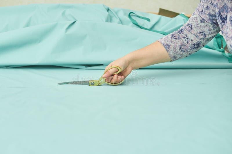 A mulher corta o material azul com tesouras douradas foto de stock