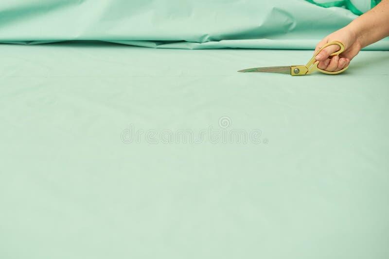 A mulher corta o material verde com tesouras douradas foto de stock