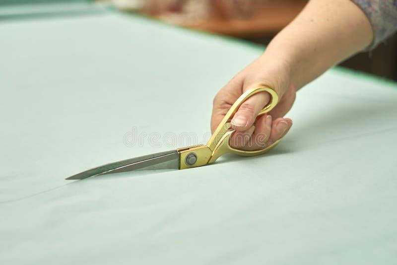 A mulher corta o material verde com tesouras douradas imagem de stock