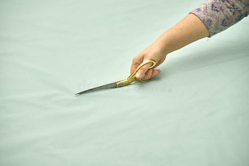 A mulher corta o material verde com tesouras douradas fotos de stock