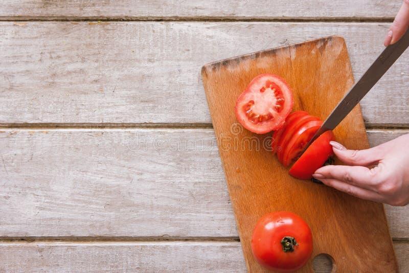 A mulher corta o tomate vermelho em partes na mesa de madeira fotos de stock royalty free