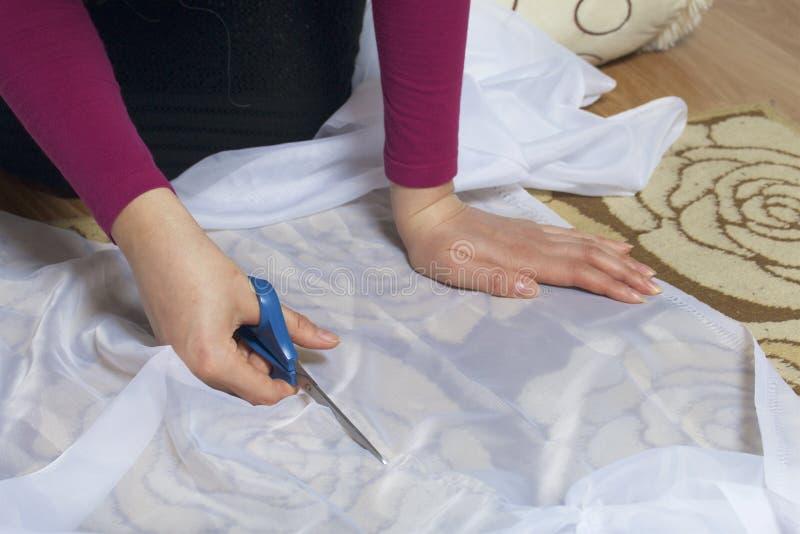 A mulher corta a tela com as tesouras para costurar cortinas na janela A tela encontra-se no assoalho Vista de acima imagem de stock royalty free
