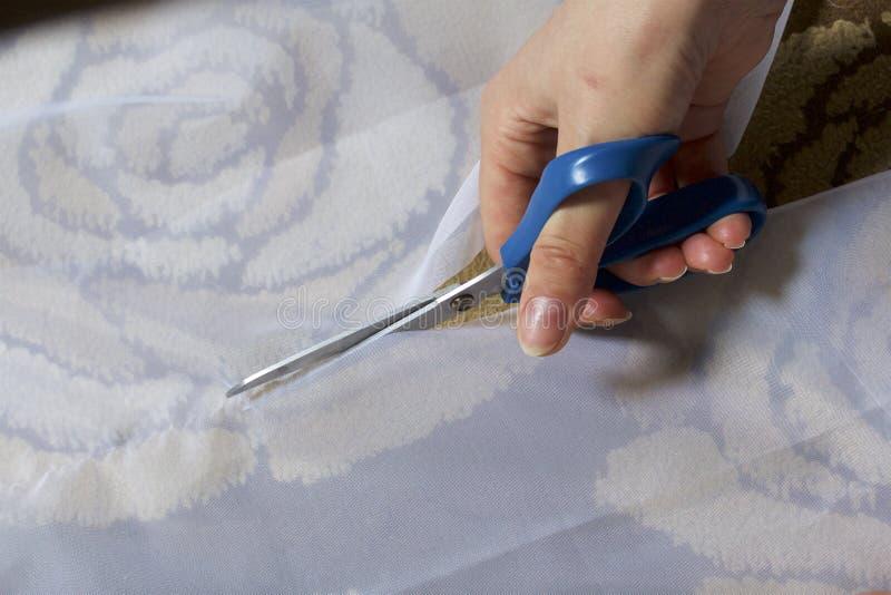 A mulher corta a tela com as tesouras para costurar cortinas na janela A tela encontra-se no assoalho Vista de acima foto de stock royalty free