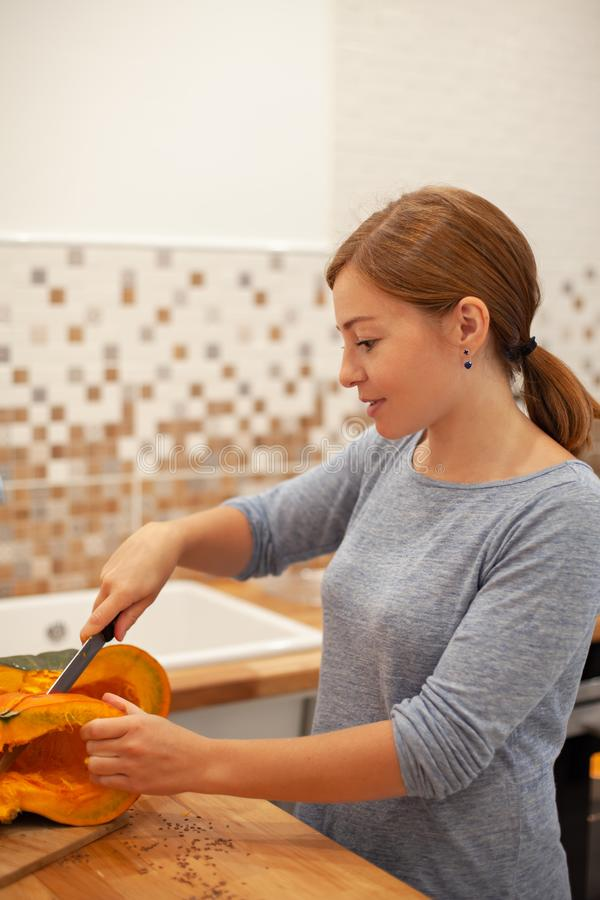 A mulher cortou a abóbora com uma faca em sua cozinha imagem de stock royalty free
