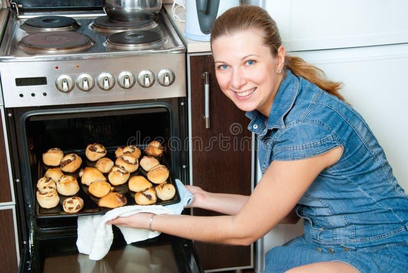 A mulher coze bolos em casa imagem de stock
