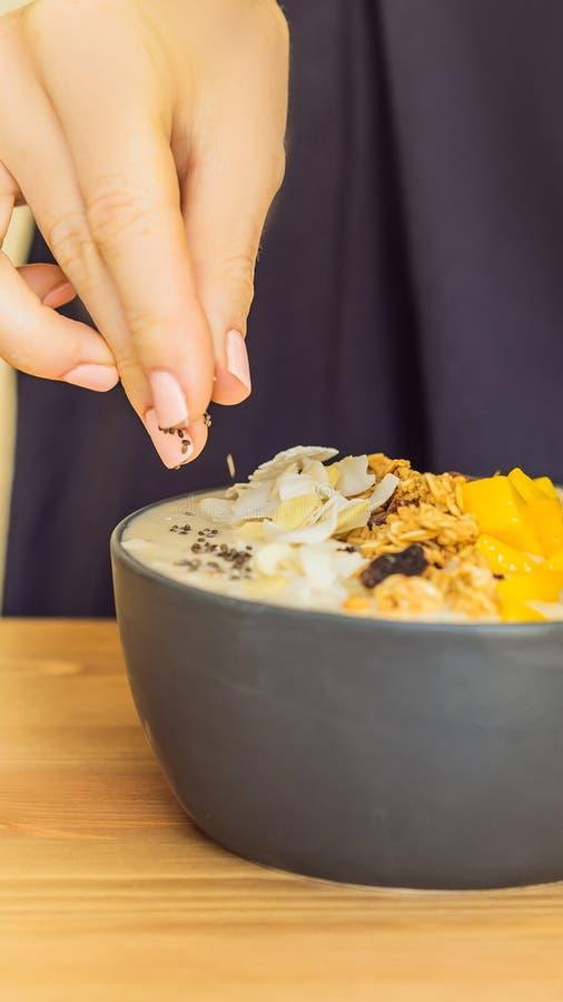 A mulher cozinha as bacias do batido feitas com manga, banana, granola, o coco raspado, o fruto do dragão, as sementes do chia e  fotografia de stock royalty free