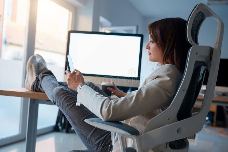 Mulher criativa do desenhista da Web que senta e que usa o telefone celular no wo foto de stock
