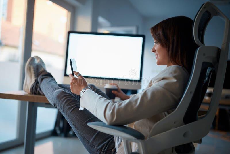Mulher criativa do designer gráfico que senta e que usa o telefone celular a fotografia de stock royalty free