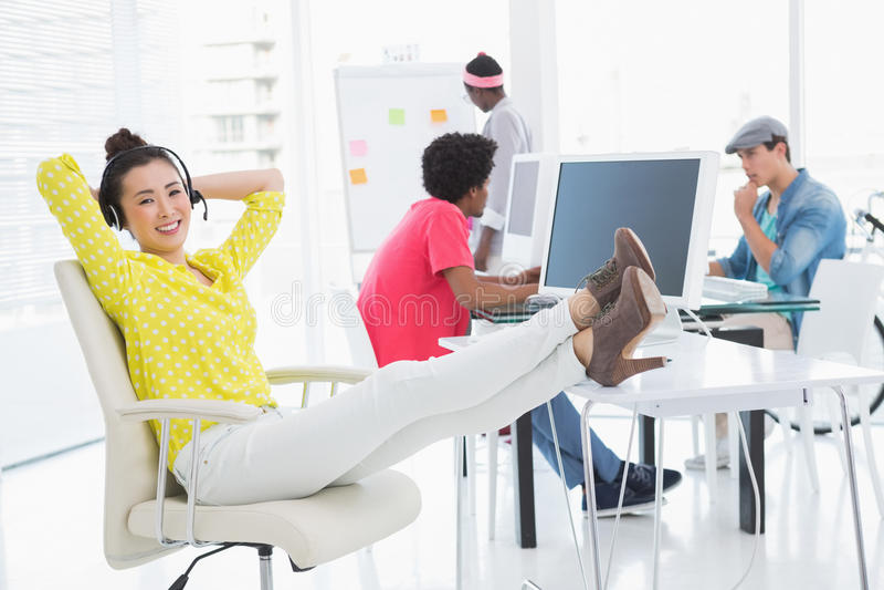 Mulher criativa nova que senta-se com pés acima foto de stock royalty free
