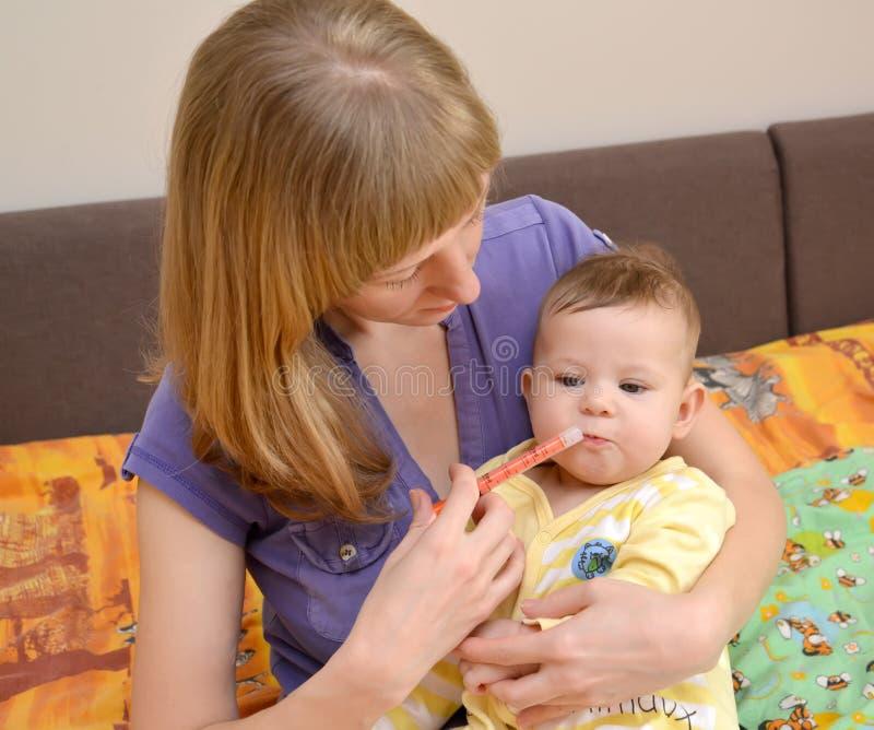 A mulher dá à medicina doente do bebê por meio do batcher foto de stock