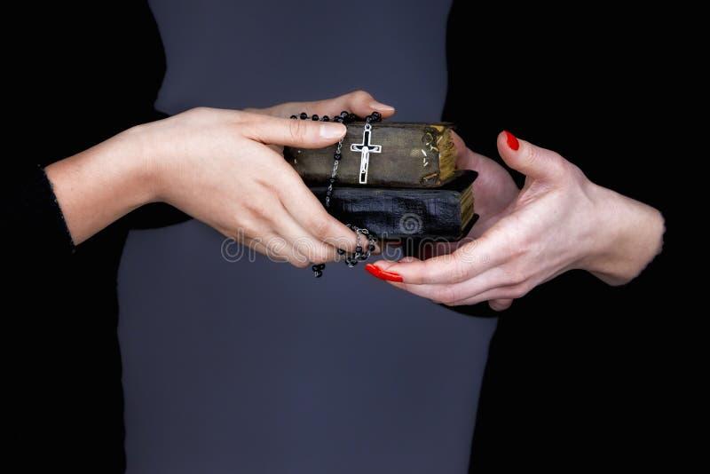 A mulher dá as dois Bíblias e rosários a uma outra mulher imagem de stock royalty free