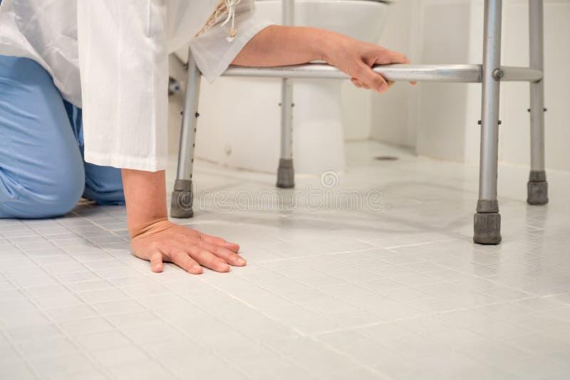 A mulher da aposentadoria caiu para baixo em um toalete imagens de stock royalty free