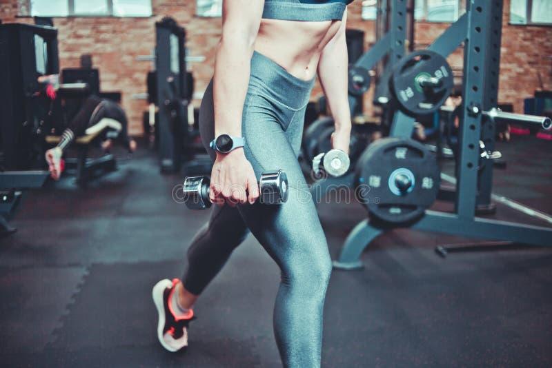 Mulher da aptidão com o corpo de esportes que exercita com pesos no gym Investe contra com pesos Conceito do treinamento foto de stock royalty free