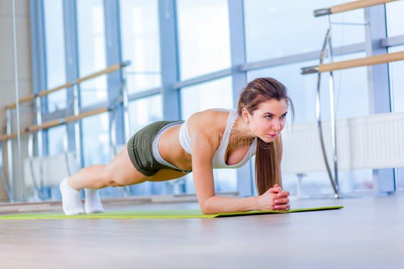 A mulher da aptidão do treinamento que faz o exercício do núcleo da prancha que dá certo para pilates traseiros do conceito da es imagens de stock royalty free