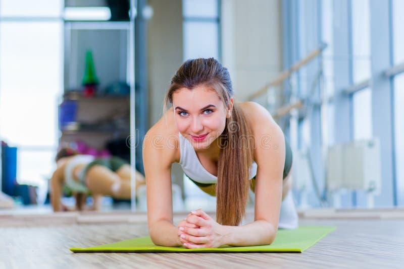 A mulher da aptidão do treinamento que faz o exercício do núcleo da prancha que dá certo para pilates traseiros do conceito da es fotos de stock royalty free