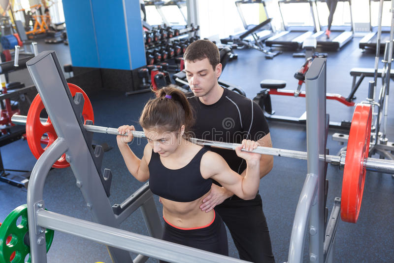 Mulher da aptidão e instrutor pessoal no gym foto de stock
