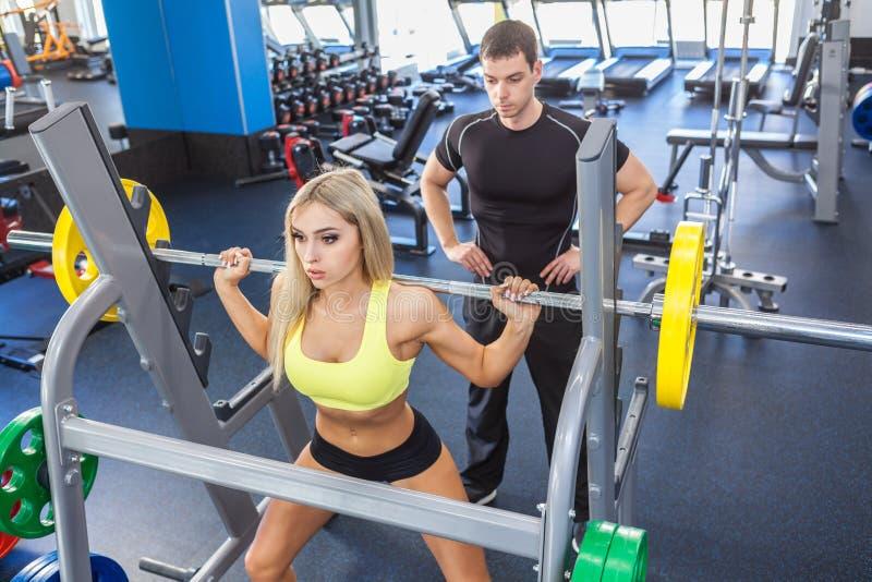 Mulher da aptidão e instrutor pessoal no gym imagem de stock royalty free