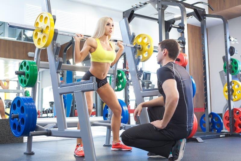 Mulher da aptidão e instrutor pessoal no gym fotografia de stock royalty free